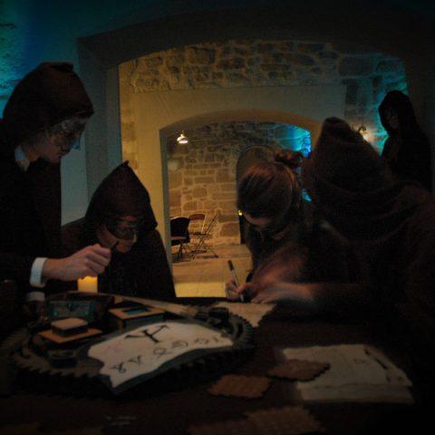 quatres joueurs en train de résoudre les enigmes d'un live escape game géant